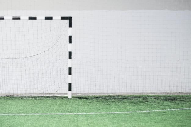 Часть пустого футбольного поля, ворот и сетки у белой стены внутри современного стадиона