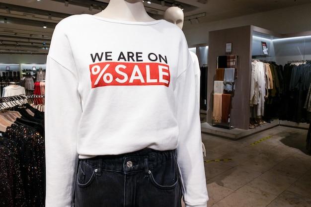 ショッピングデパートでのセールテキスト付きのカジュアルな服を着た女性のマネキンの一部