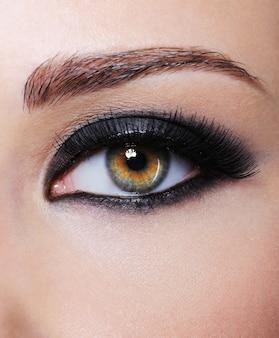明るい黒のグラマーメイク-マクロ撮影で目を持つ女性の一部