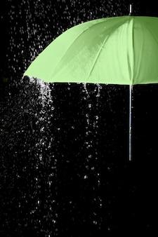 黒の背景と雨滴の下の緑の傘の一部。ビジネスとファッションのコンセプト。