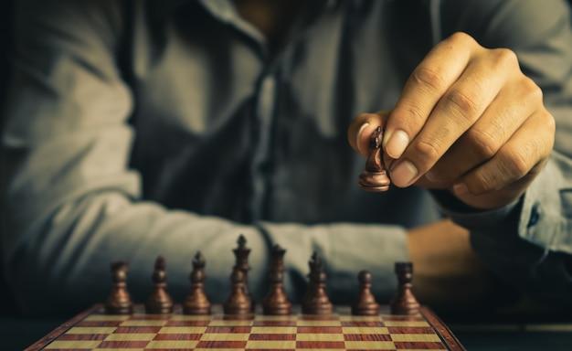 인간의 손의 일부는 레트로 컬러 톤의 체스 보드에 체스 그림을 이동