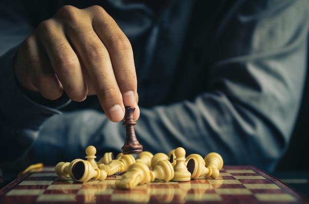 인간의 손의 일부는 레트로 컬러 톤의 체스 보드에 체스 그림을 이동 프리미엄 사진
