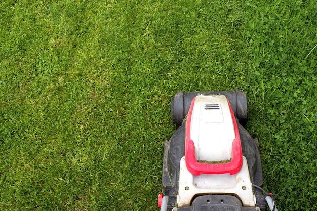 モダンな庭の緑の芝生の芝刈り機の一部。庭と裏庭の風景芝刈り機。ガーデン電動工具機器。