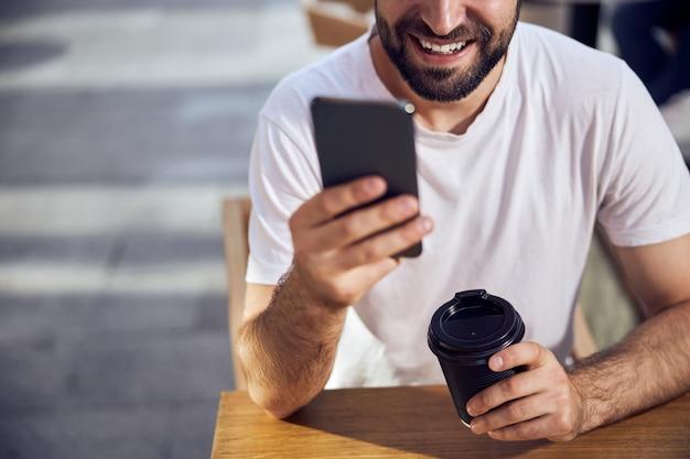커피와 함께 카페 테이블에 앉아 스마트 폰을 찾고 남자 얼굴의 일부를 닫습니다