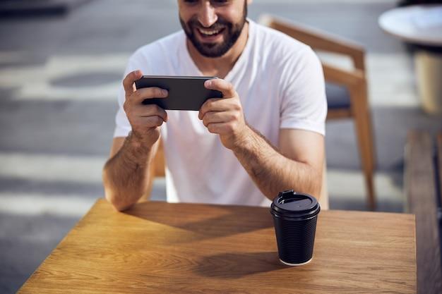 카페에서 커피와 함께 테이블에 앉아 스마트 폰을 바라 보는 남자 얼굴의 일부