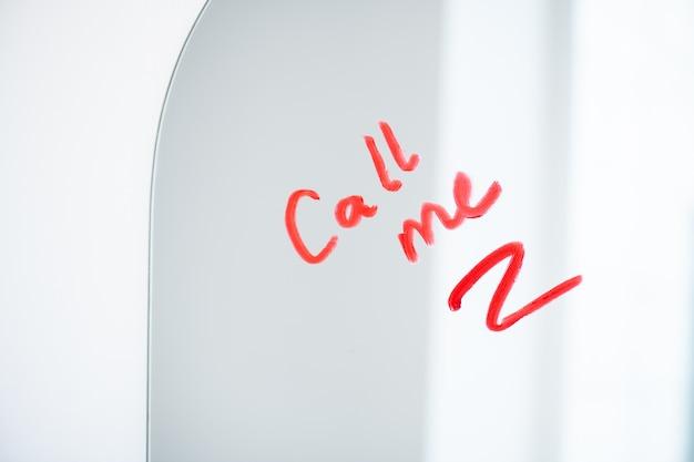 好色な若い女性が赤または深紅の口紅で書いた電話を求める鏡の一部