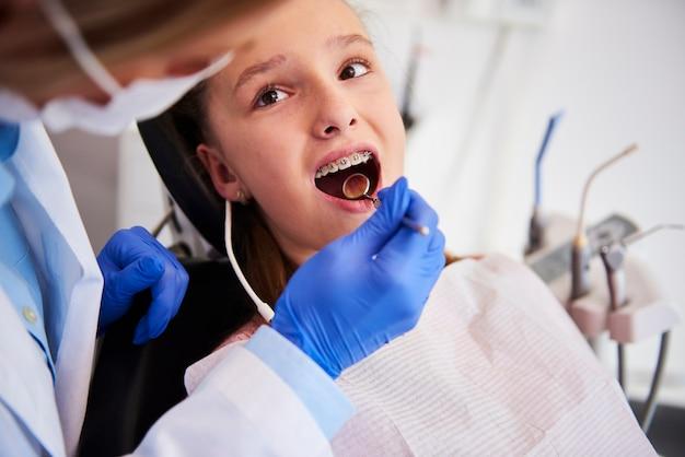 Часть ортодонта, осматривающего детские зубы в кабинете стоматолога