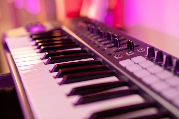 음악가가 새로운 음악을 만들고 수정하는 데 사용되는 흑백 키, 버튼 및 많은 슬라이더가있는 피아노 키보드의 일부