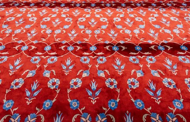 イスラム教徒のモスクのレッドカーペットまたは敷物の一部。イスタンブールのブルーモスクの祈りのマット
