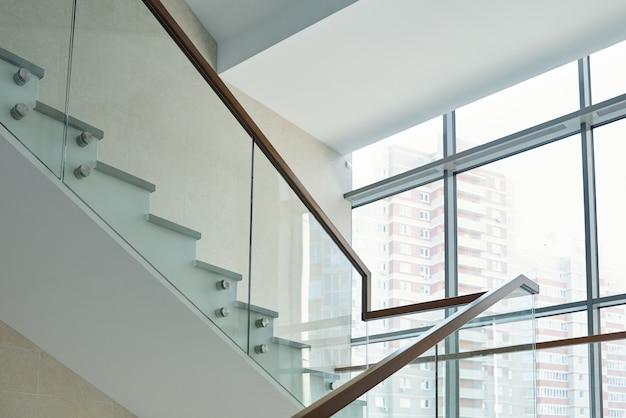 Часть лестницы с перилами и большим окном внутри нового современного бизнес-центра или многоэтажного офисного здания.