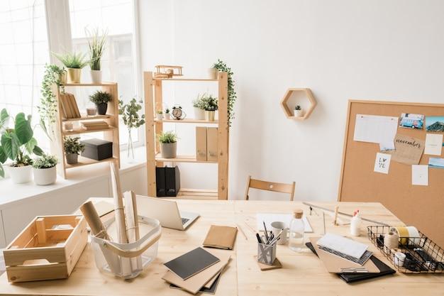Часть интерьера студии с письменным столом у окна, домашними растениями на полках, бумагами, ноутбуком и другими вещами для работы