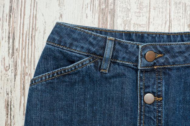 Часть синей джинсовой юбки. деревянный фон, модная концепция