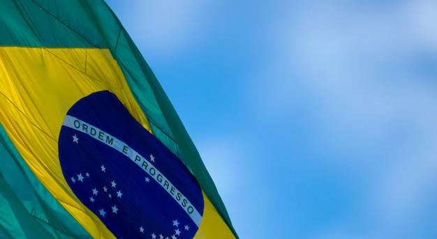 焦点がぼけた空の言葉の順序と進歩を伴うブラジルの旗の一部