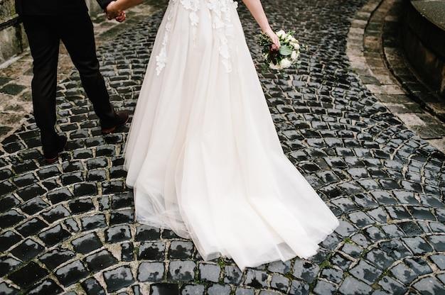 오래 된 돌 포장에 오래 된 도시에서 신부의 드레스와 신랑의 정장의 일부입니다.