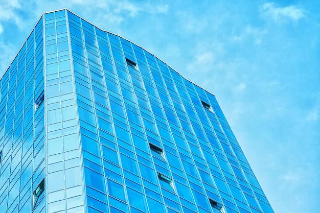 空を背景にガラス張りの窓がある建物の一部。