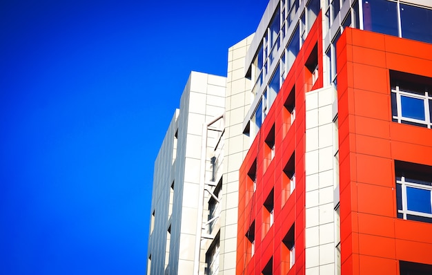 빨간색 벽, 정사각형 창문, 파란색 거울 유리가 있는 현대적인 건물의 정면 일부입니다. 밝고 화창한 날 현대적인 스타일의 건축과 첨단 기술
