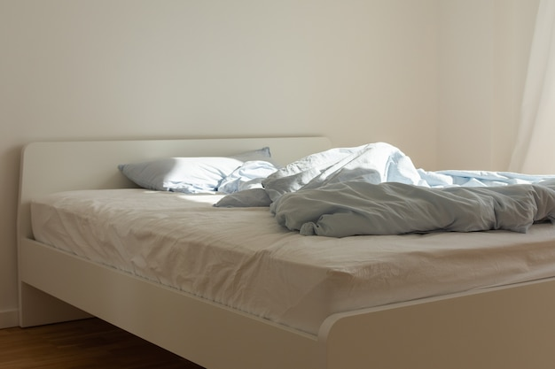 Часть интерьера дома или отеля, кровать после сна утром на солнце, белая кровать с матрасом и синее постельное белье