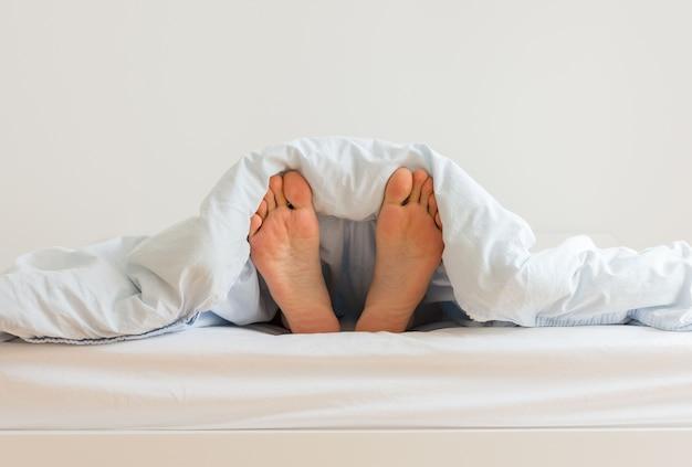 Часть интерьера дома или отеля, мужские ноги выглядывают из-под одеяла, мужчина спит на белой кровати с синим постельным бельем по утрам