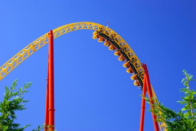 Часть петли на американских горках во время проезда тележек вверх ногами на фоне голубого неба