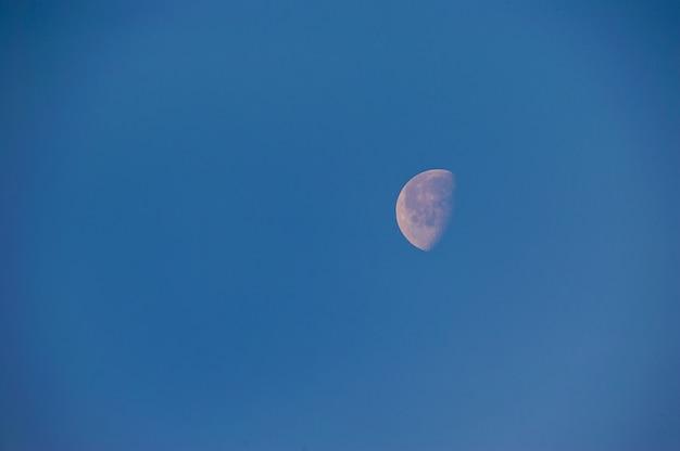밤에 어두운 푸른 하늘에 달의 일부