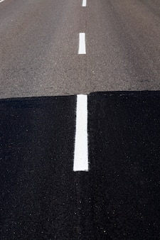 도로의 건설 또는 재건 수리를 위해 연결된 기존 및 새로운 아스팔트 도로의 일부인 아스팔트에는 흰색 도로 표시가 표시되어 있습니다.