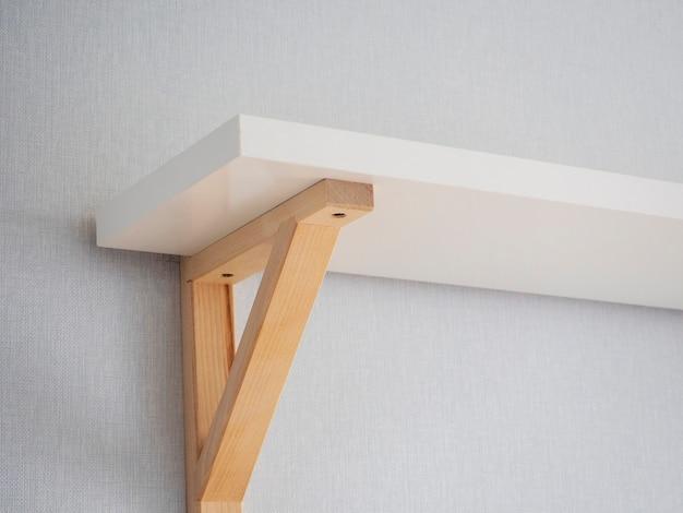 壁の棚の一部は白で、木製の脚が付いています。モダンなインテリアデザイン