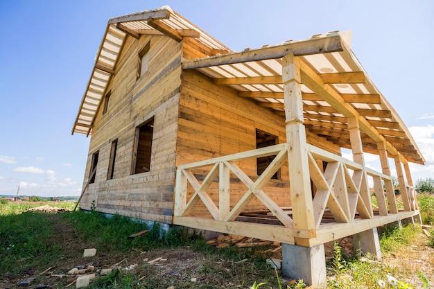 Часть незаконченного деревянного экологического традиционного коттеджа из натуральных лесоматериалов с крутой рамой крыши и прилегающей террасой с декоративными перилами под строительство в зеленом районе.