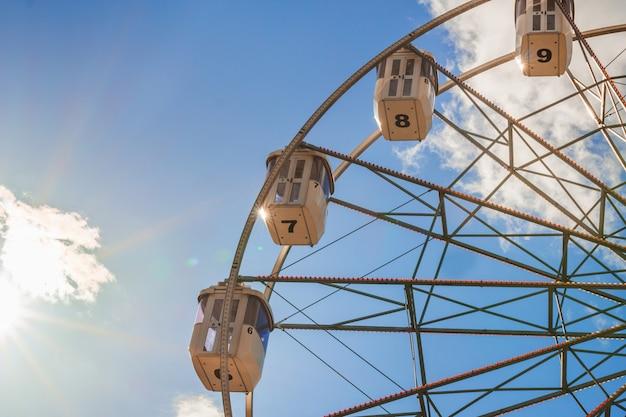 Часть белого колеса обозрения на фоне голубого неба