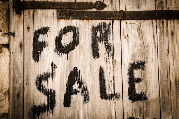 판매를 위한 비문이 있는 나무 문의 일부