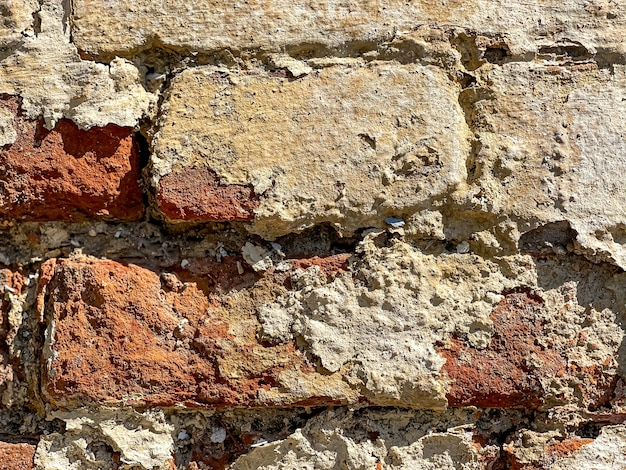 Part of an old brick wall with bricks close up.