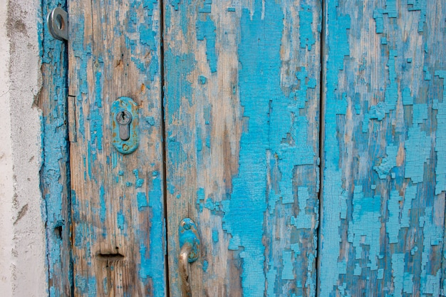 Part of an old wooden door with peeling blue paint and a keyhole
