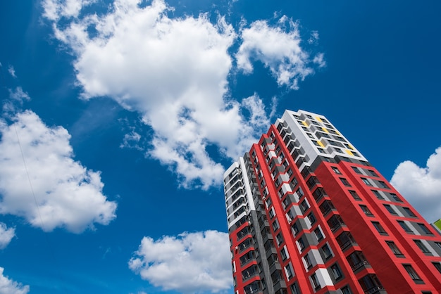 Part of a red modern house against a blue sky with clouds