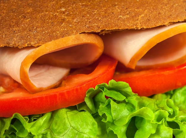 Part of sandwich with lettuce, tomatoes, ham. closeup