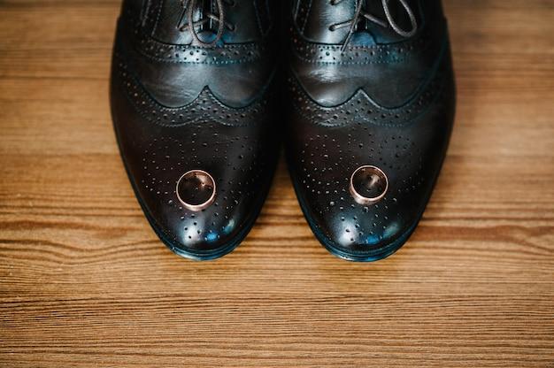부분 세련된 남자 검은 신발, 밝은 갈색 테이블에 누워 두 개의 반지를 결혼. 소박한 나무 배경에 웨딩 액세서리 신랑. 아이디어 구성. 휴가 개념. 평평한 평신도. 평면도.