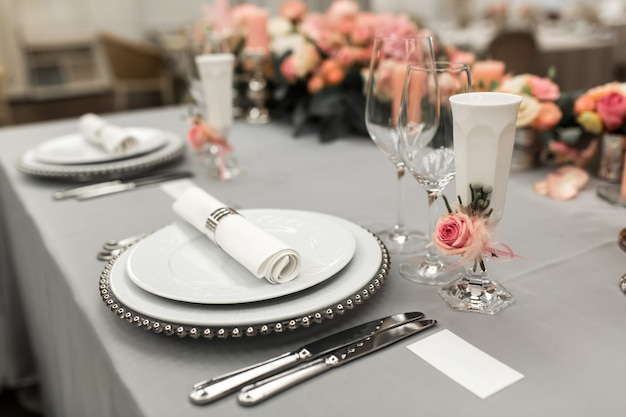 Part of stylish table setting with plate and cutlery. nearby lies a white business card. copy space