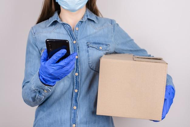 アルバイトのコンセプト。コピーの空きスペースで灰色の壁に隔離された段ボール箱を保持している彼女の電話の画面を見ている学生のトリミングされたクローズアップ写真