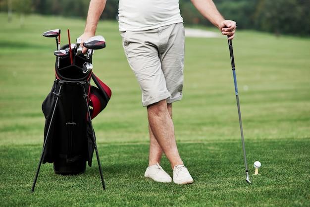골프 장비와 푸른 잔디에 서있는 남자의 부분보기.