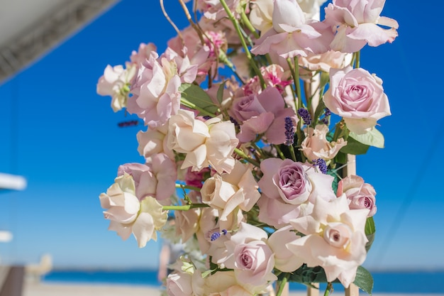 Part of the wedding arch decorated with fresh flowers is set on the blue sky