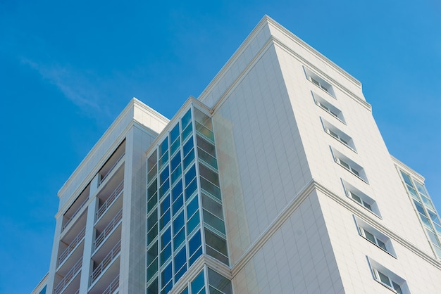 Part of a white multi-storey residential building with windows and balconies against the blue sky
