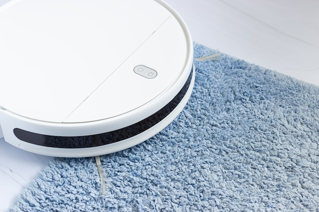 Part of a white robot vacuum cleaner on a blue carpet, side view