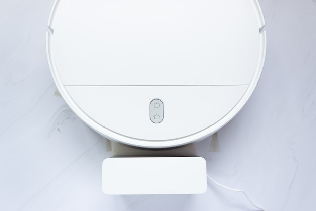 Part of a white robot vacuum cleaner and charger, top view