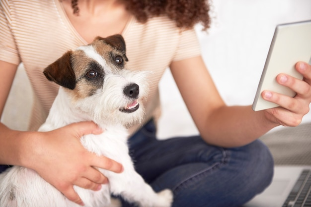 Part of woman embracing her dog and using mobile phone