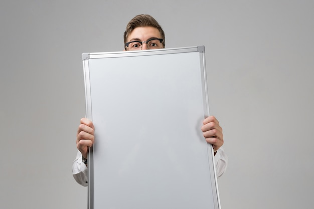 Part of young man wearing glasses with clean magnetic blank white board in his hands
