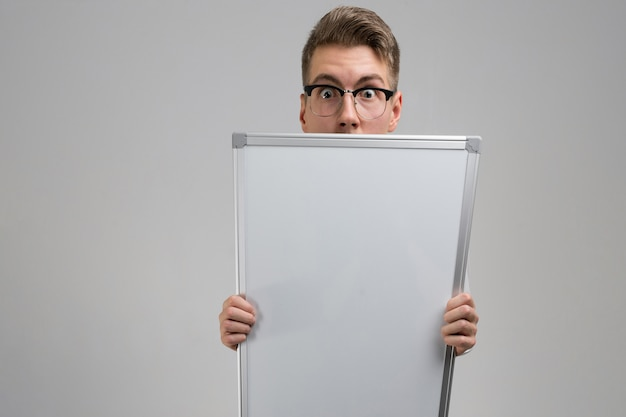 Part of young man wearing glasses with clean magnetic board in his hands isolated on white tshirt