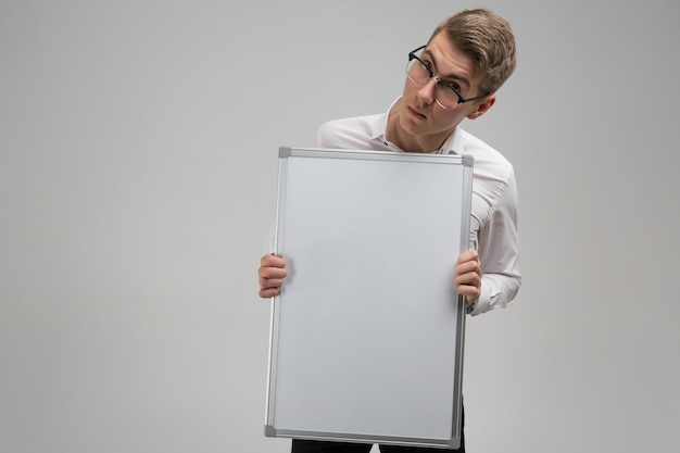 Part of young man wearing glasses with clean magnetic board in his hands isolated on white