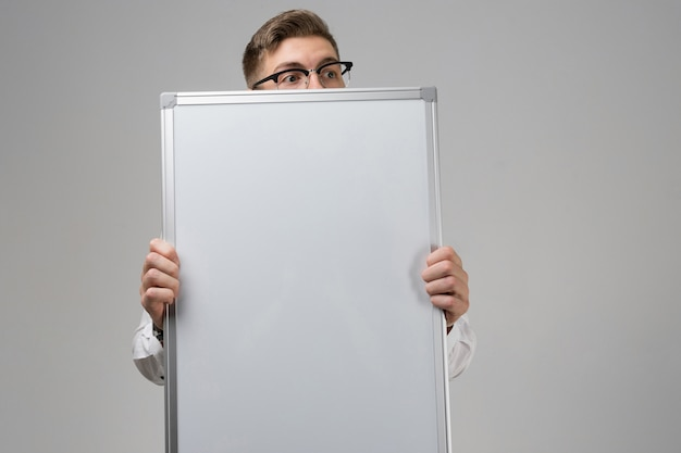 Part of young man wearing glasses with clean magnetic board in his hands isolated  white