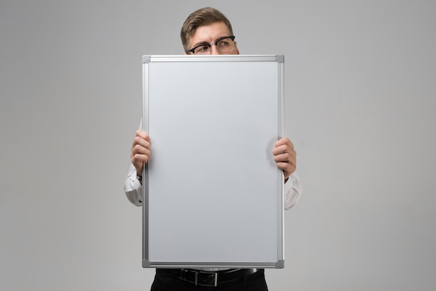 Part of young man wearing glasses with clean magnetic board in his hands isolated
