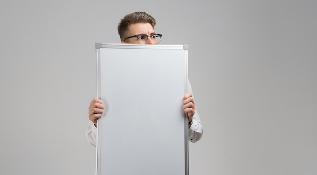 Part of young man wearing glasses with clean magnetic board in his hands