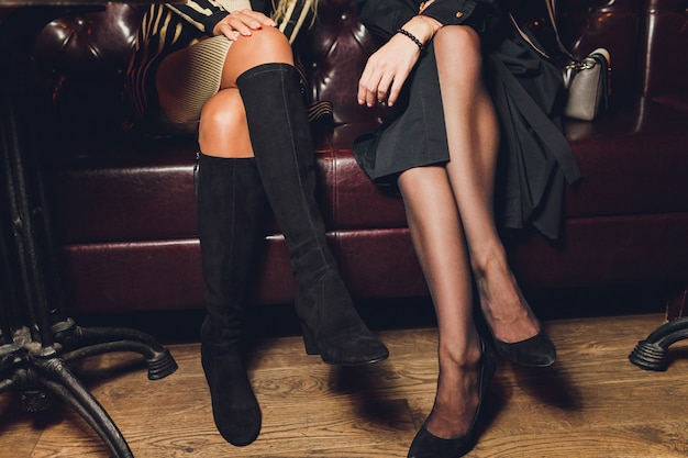 Part of young women with perfect legs keeping their legs crossed at knee while sitting on sofa at the shoe store.