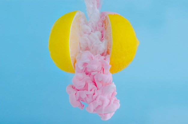 Partial focus of dissolving pink poster color in water drop between lemons on blue background.